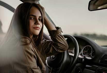 meisje zittend achter het stuur van een lesauto om het autorijbewijs te halen