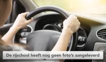 Vrouw met twee handen op het stuur van een auto