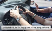 Vrouw met twee handen op het stuur van lesauto met instructeur van rijschool