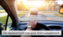 Een hand op het stuur van een auto