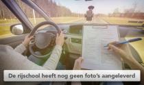 Leerling van rijschool rijd af met examinator ernaast met beoordelingsformulier in de hand